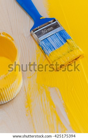 The process of staining painting wood surfaces with a brush and acrylic yellow paint