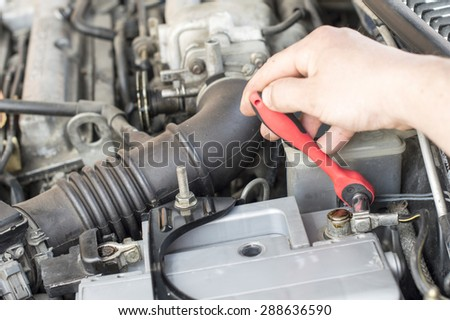 The process of tightening bolts to fix the the vehicle battery