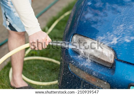 The process of washing cars headlights with a hose with water in the yard