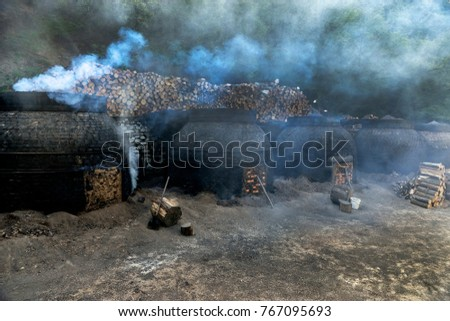 The production of charcoal in a traditional manner in the forest
