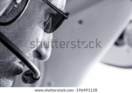 The profile of a man wearing sunglasses and a headset.
