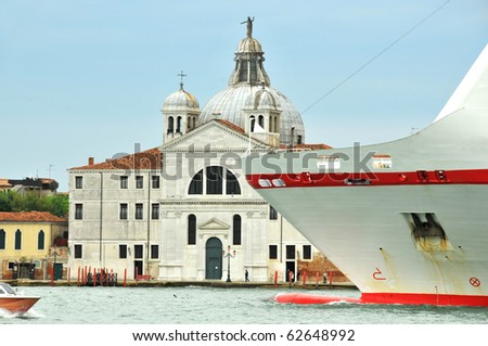 the prow of a large cruiser passes in front of a church in the Venice lagoon - stock photo