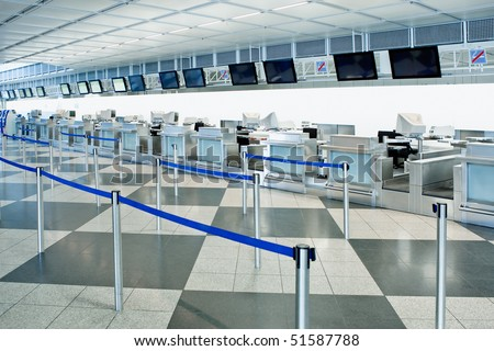 The public check-in area of an airport with crowd control barriers - stock photo