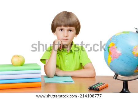 The pupil with books and a globe sitting at the table