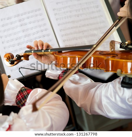 The pupils playing the violin in front of sheet music. - stock photo