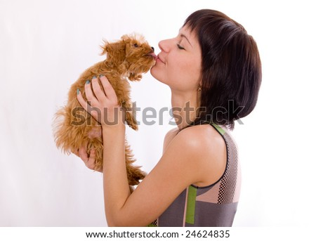 The puppy kisses the young charming girl