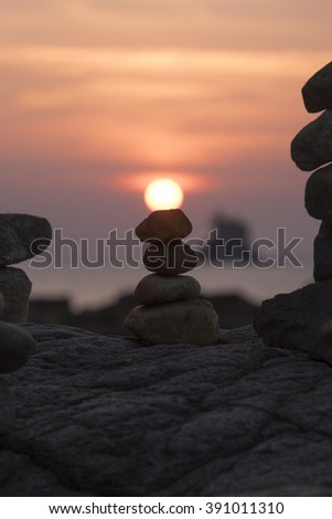 The pyramid of pebbles on the sea shore in the evening