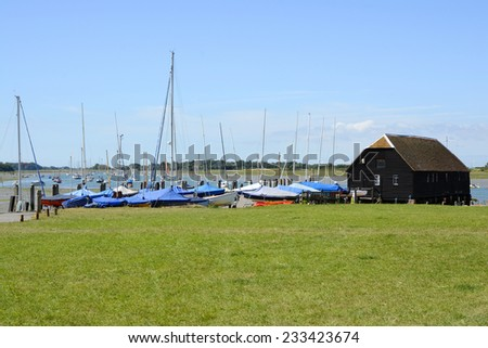 The Quay at Bosham in West Sussex. England. At low tide with moored and beached boats - stock photo