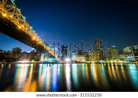The Queensboro Bridge and Manhattan skyline at night, seen from Roosevelt Island, New York. - stock photo