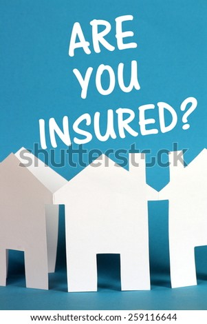 The question Are You Insured above a chain of white paper houses on a blue background - stock photo