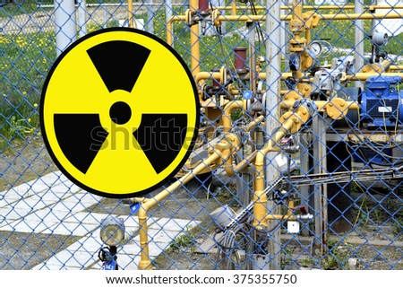 The radioactivity sign on the fence of the facility - stock photo