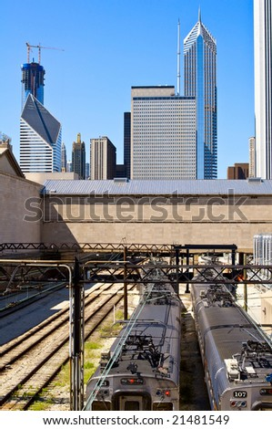 The railway runs into the heart of downtown Chicago. Trains in the foreground and skyline in the background.