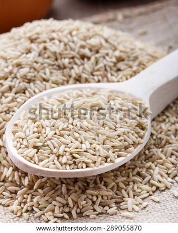 The raw brown rice on the wooden spoon - stock photo