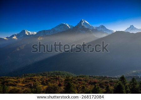 The ray of light is spotting over the Annapurna mountain range from Poon Hill viewpoint in the morning. - stock photo
