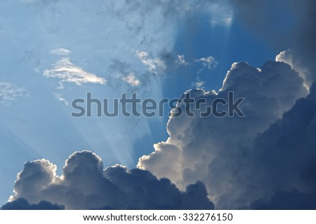 The rays of the sun, making their way from behind the clouds - stock photo