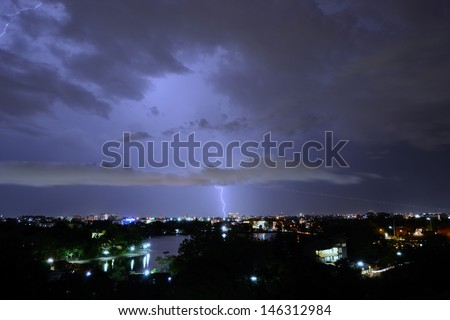 The real lightening over the city and the airplane take off at night time