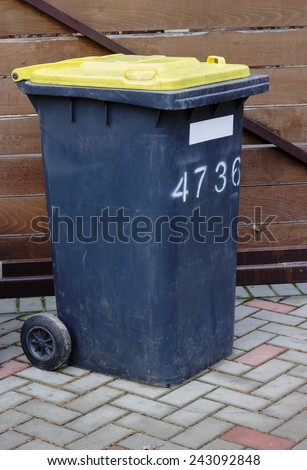 The real old dirty plastic garbage container with a yellow cover - stock photo