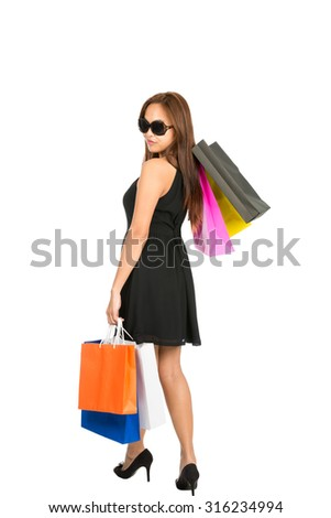 The rear of a beautiful Asian female shopper wearing a black elegant dress walking away with colorful shopping bags at side and slung over looking back over her shoulder. Isolated white full length - stock photo