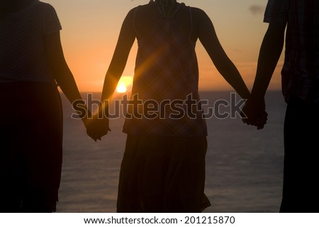 The rear view of the man and two women hold their hands each other while staring at the sunset - stock photo