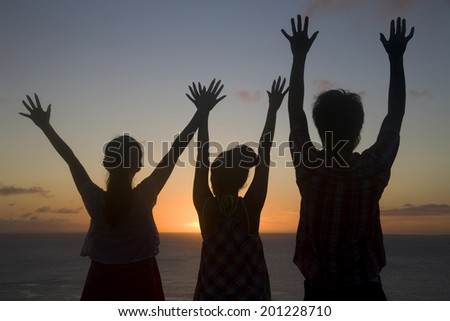 The rear view of the man and two women spreading both hands to the sky at dusk