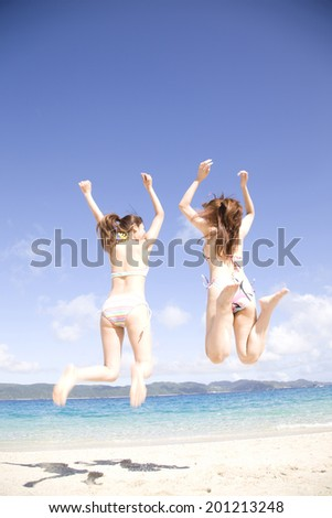 The rear view of two women with a swimming suit jumping on the beach