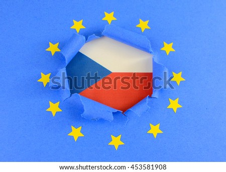 The red, blue and white flag of Czechoslavakia is shown behind the torn open center of the blue flag of the European Union with gold stars. The EU flag is highly textured construction paper.