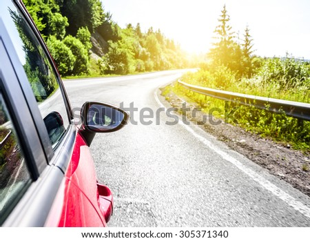 The red car hurtling the highway beautiful countryside