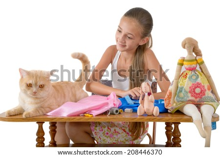 The red cat prevents the girl to sew toys from fabric - stock photo