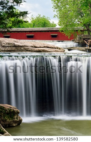 The red Cataract Covered Bridge spans Indiana's Mill Creek just upstream from beautiful Upper Cataract Falls. - stock photo