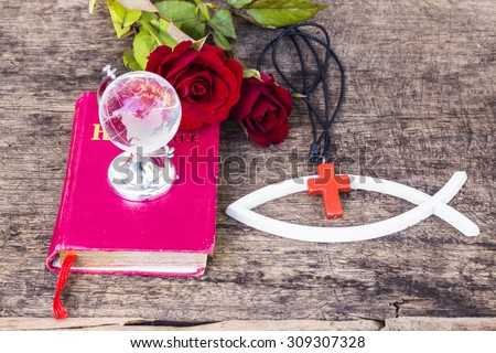 The red cross  over the white christian fish and the world globe model on the red bible with red roses  on wooden background, world mission concept.  - stock photo