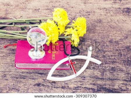 The red cross  over the white christian fish and the world globe model on the red bible yellow flowers on wooden background, world mission concept.  - stock photo