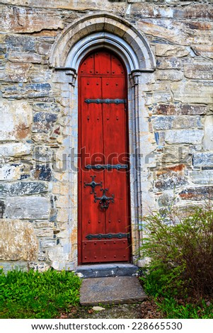The red door to the medieval stone church - stock photo