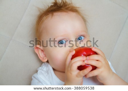 The red-haired and blue-eyed boy eating an apple