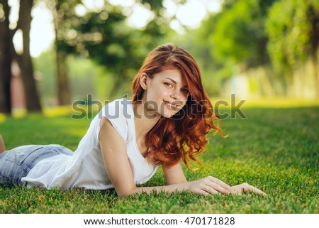 The red-haired girl enjoying the outdoors and the warmth lying on the grass