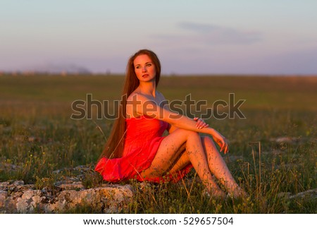 The red-haired girl in field at sunset