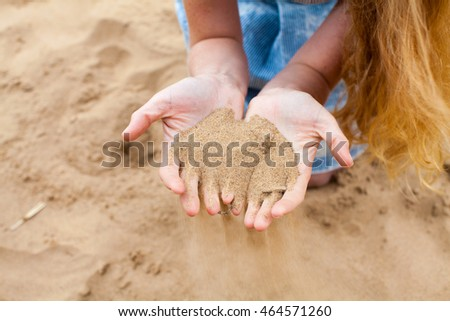 The red-haired girl on the beach holding hands in the sand. Summer. Hair develop. It's a nasty day. Beautiful girl with red hair playing with sand. Time