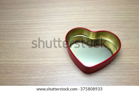 The red heart shape box on the wooden background for Valentine's day.