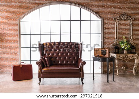 The red leather sofa with a big luggage in vintage room - stock photo