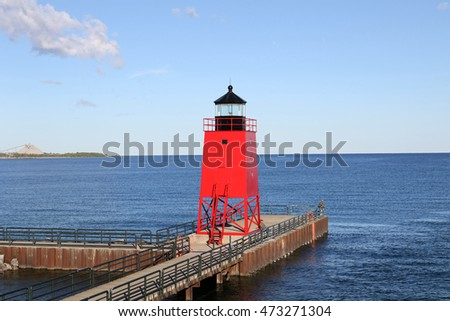 The red lighthouse at the entrance to the harbor at Charlevoix, Michigan from Lake Michigan.