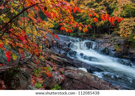 The red maples leaves frame this beautiful waterfall in Algonquin park at the peak of the fall colors. - stock photo