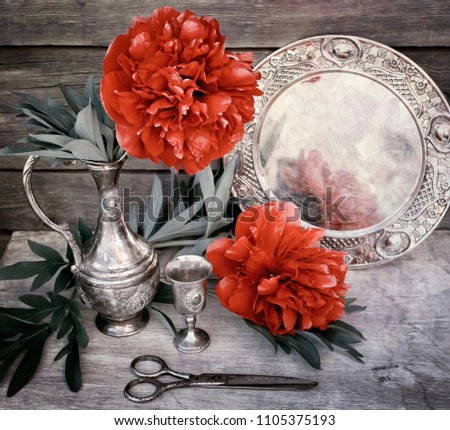 The red peony in a metal jug costs against the background of a wooden wall. The summer and spring blossoming scene.