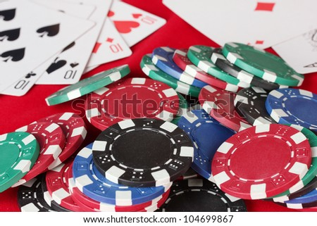 The red poker table with playing cards and poker chips