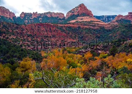 The red rocks overlook the canyon full of color on a fall cloudy day - stock photo