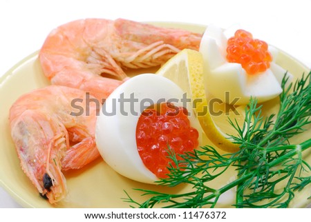 The red salmon caviar and cooked prawns on porcelain dish