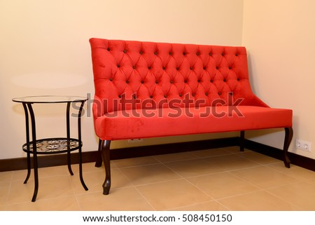 The red sofa and metal coffee table stand at a wall in a drawing room