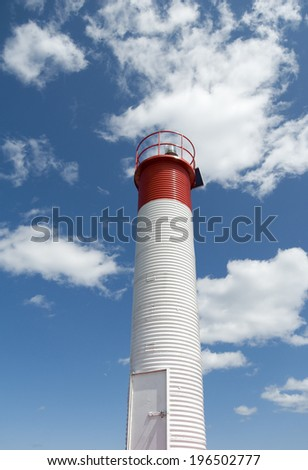 The red top of a white light house in the clouds.