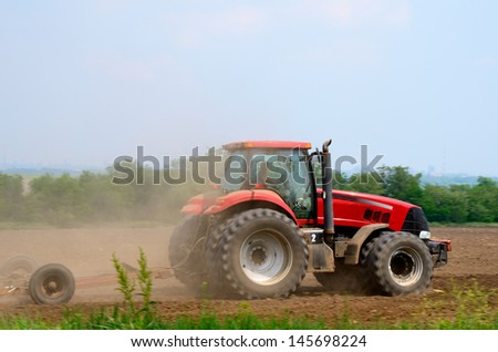The red tractor in a field - stock photo