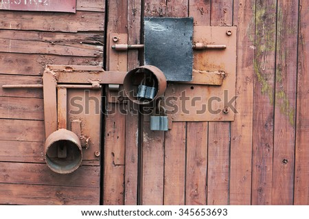 The red wooden shed is locked on three padlocks closeup background