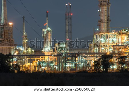 The refinery in the blue sky twilight time with lighting from the tower and fire from burner stack house - stock photo