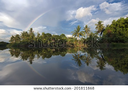 The reflect of rainbow in Kinabantangan river. Borneo - stock photo